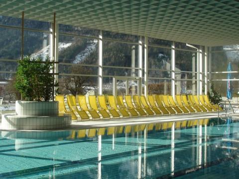 Innenansicht vom Panoramahallenbad Spital am Pyhrn mit gelben Liegestühlen in der Nähe vom JUFA Hotel Pyhrn-Priel. Der Ort für erholsamen Familienurlaub und einen unvergesslichen Winter- und Wanderurlaub.