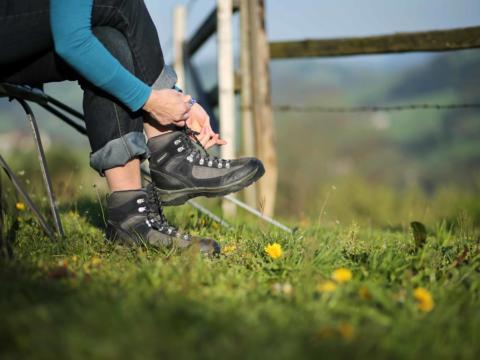 Dame beim Schuhebinden am Pilgerweg