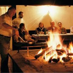 Rauchkuchl mit Menschen am Feuer im JUFA Hotel Schloss Röthelstein. Der Ort für märchenhafte Hochzeiten und erfolgreiche und kreative Seminare.