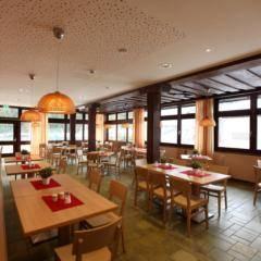 Gemütliches Restaurant mit Fensterfront im JUFA Hotel Altenmarkt. Der Ort für erholsamen Familienurlaub und einen unvergesslichen Winterurlaub.