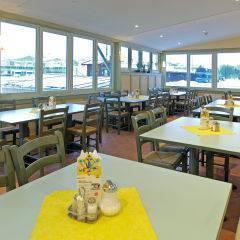 Gemütliches Restaurant mit Fensterfront im JUFA Hotel Kaprun. Der Ort für erholsamen Familienurlaub und einen unvergesslichen Winter- und Wanderurlaub.