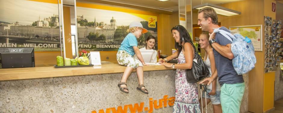 Familien beim Einchecken im JUFA Hotel Salzburg City. JUFA Hotels bietet erlebnisreichen Städtetrip für die ganze Familie und den idealen Platz für Ihr Seminar.