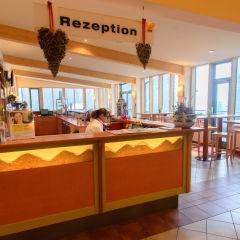 Rezeption mit Rezeptionistin und mit Bartischen im JUFA Hotel Altaussee. Der Ort für erholsamen Familienurlaub und einen unvergesslichen Winter- und Wanderurlaub.