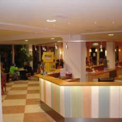 Rezeption und Lobby mit Menschen im JUFA Hotel Kaprun. Der Ort für erholsamen Familienurlaub und einen unvergesslichen Winter- und Wanderurlaub.