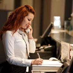 Frau telefoniert an der Rezeption. JUFA Hotels bietet erholsamen Familienurlaub und einen unvergesslichen Winter- und Wanderurlaub.