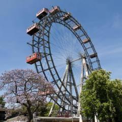 Riesenrad im Prater Wien im Sommer mit Bäumen bei hellblauen Himmel. JUFA Hotels bietet erlebnisreichen Städtetrip für die ganze Familie und der ideale Platz für Ihr Seminar.