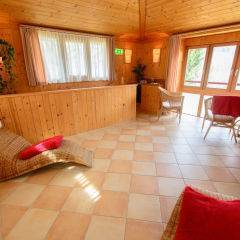 Ruheraum mit Ratanliegen im Wellnessbereich im JUFA Hotel Grundlsee. Der Ort für tollen Sommerurlaub an schönen Seen für die ganze Familie.