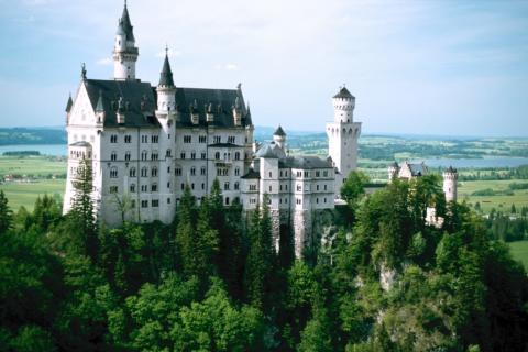 Schloss Neuschwanstein in Bayern mit Landschaft im Sommer.