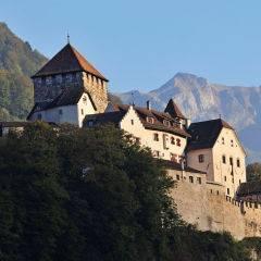 Schloss Vaduz in Liechtenstein mit Berglandschaft im Sommer. JUFA Hotels bietet erholsamen Familienurlaub und einen unvergesslichen Winter- und Wanderurlaub.