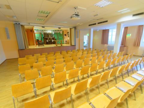 Gut ausgestatteter Seminarraum mit Bühne und Bestuhlung im JUFA Hotel Kaprun. Der Ort für erholsamen Familienurlaub und einen unvergesslichen Winter- und Wanderurlaub.