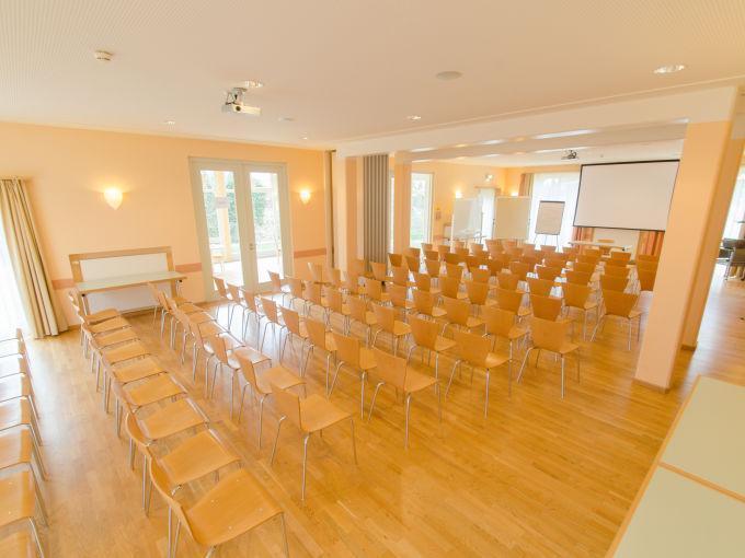 Seminarraum mit Bestuhlung und Beamerwand im JUFA Hotel Nördlingen. Der Ort für kinderfreundlichen und erlebnisreichen Urlaub für die ganze Familie.