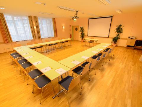 Gut ausgestatteter Seminarraum mit U-Form und Beamerwand im JUFA Hotel Altaussee. Der Ort für erholsamen Familienurlaub und einen unvergesslichen Winter- und Wanderurlaub.