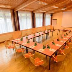 Gut ausgestatteter Seminarraum mit U-Form und Fenstern im JUFA Hotel Grundlsee. Der Ort für tollen Sommerurlaub an schönen Seen für die ganze Familie.