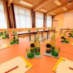 Gut ausgestatteter Seminarraum mit U-Form und Notizblöcken im JUFA Hotel Grundlsee. Der Ort für tollen Sommerurlaub an schönen Seen für die ganze Familie.