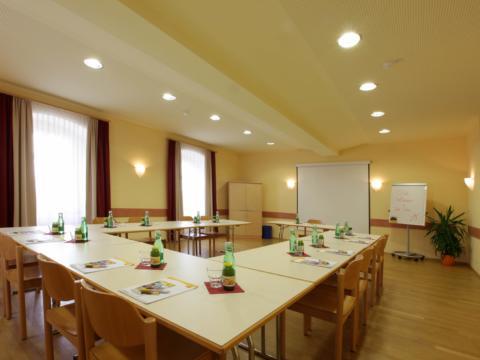 Gut ausgestatteter Seminarraum mit U-Form und Beamerwand im JUFA Hotel Seckau. Der Ort für erholsamen Familienurlaub und einen unvergesslichen Winter- und Wanderurlaub.