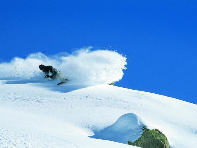 Snowboarder im Pulverschnee in Tirol. JUFA Hotels bietet erholsamen Familienurlaub und einen unvergesslichen Winterurlaub.