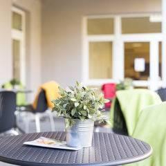 Gemütliche Sonnenterrasse mit Tischen im JUFA Hotel Graz City. Der Ort für erlebnisreichen Städtetrip für die ganze Familie und der ideale Platz für Ihr Seminar.