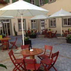Gemütliche Sonnenterrasse mit Sonnenschirme im JUFA Hotel Meersburg. Der Ort für tollen Sommerurlaub an schönen Seen für die ganze Familie.