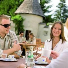 Erwachsene sitzen auf der Sonnenterrasse beim JUFA Hotel Schloss Röthelstein. Der Ort für märchenhafte Hochzeiten und erfolgreiche und kreative Seminare.