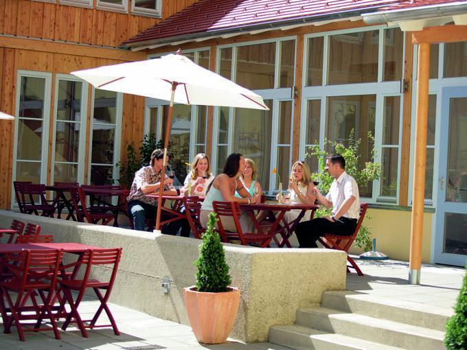 Gemütliche Sonnenterrasse mit Erwachsenen beim Weintrinken im JUFA Hotel Seckau. Der Ort für erholsamen Familienurlaub und einen unvergesslichen Winter- und Wanderurlaub.