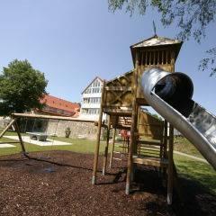 Spielplatz mit Rutsche im Sommer am JUFA Hotel Nördlingen. Der Ort für kinderfreundlichen und erlebnisreichen Urlaub für die ganze Familie.