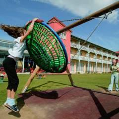 Kinder schauklen auf dem Spielplatz am JUFA Hotel Gnas - Sport-Resort. Der Ort für erfolgreiches Training in ungezwungener Atmosphäre für Vereine und Teams.