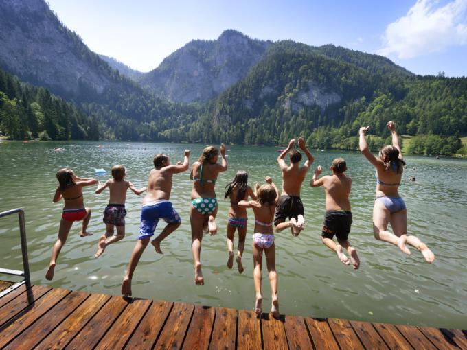 Teens springen vom Steg in den Gleinkersee in Oberösterreich im Sommer. JUFA Hotels bietet tollen Sommerurlaub an schönen Seen für die ganze Familie.