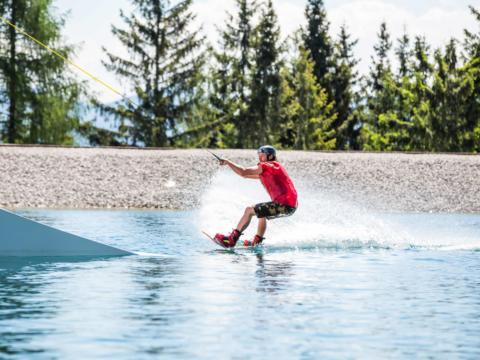 Mann beim Wakeboarden im Wasser bei WakeAlps auf der Mariazeller Bürgeralpe im JUFA Hotel Urlaub. JUFA Hotels bietet erholsamen Familienurlaub und einen unvergesslichen Winterurlaub.