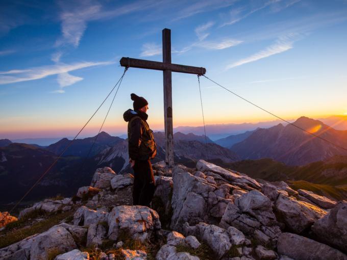 Wanderer auf dem Augstenberg mit Bergaussicht mit Morgenstimmung. JUFA Hotels bietet erholsamen Familienurlaub und einen unvergesslichen Winter- und Wanderurlaub.