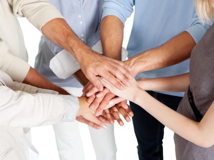 Erwachsene legen die Hände übereinander als Zeichen einer erfolgreichen Weiterbildung in den JUFA Hotels. Der Ort für erfolgreiche und kreative Seminare in abwechslungsreichen Regionen.