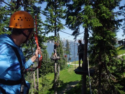 Erwachsene im Hochseilgarten im Abenteuerpark Planai in Schladming-Dachstein in der Nähe vom JUFA Hotel Schladming. Der Ort für erholsamen Familienurlaub und einen unvergesslichen Winter- und Wanderurlaub.