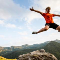 Frau springt auf der Planneralm in die Luft in der Nähe von JUFA Hotels. Der Ort für erholsamen Familienurlaub und einen unvergesslichen Winter- und Wanderurlaub.