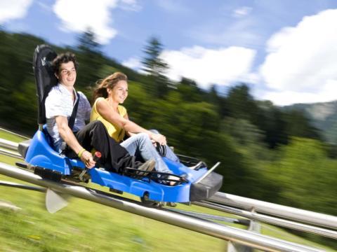 Paar beim Sommerrodeln auf dem Alpine Coaster am Golm in Montafon in Vorarlberg in der Nähe von JUFA Hotels. Der Ort für erholsamen Familienurlaub und einen unvergesslichen Winter- und Wanderurlaub.