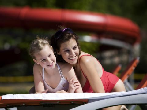 Sie sehen eine Mutter und ihre Tochter auf einer Sonnenliege im Asia Spa. JUFA Hotels bietet erholsamen Thermenspass für die ganze Familie.