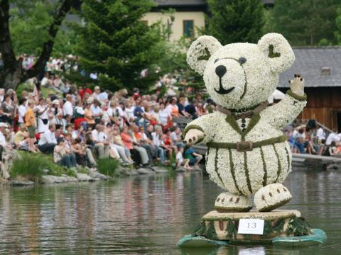 Sie sehen eine Narzissenfigur in der Form eines Bärens auf dem Narzissenfest in Aussee vor Publikum. JUFA Hotels bietet kinderfreundlichen und erlebnisreichen Urlaub für die ganze Familie.