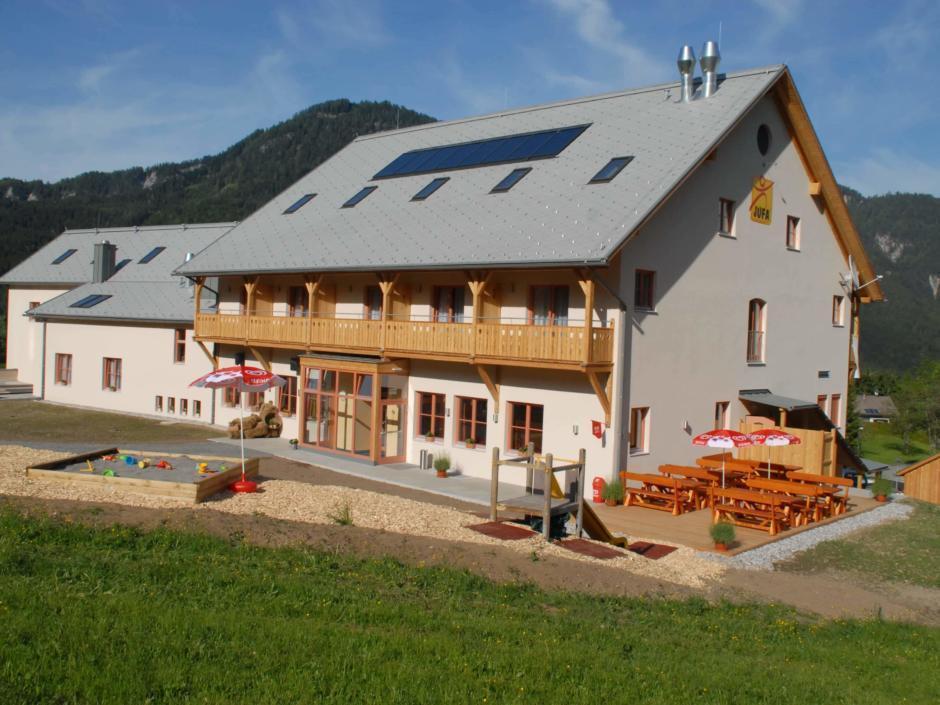 Aussenansicht mit Spielplatz und Terrasse vom JUFA Hotel Gitschtal Landerlebnis. Der Ort für kinderfreundlichen und erlebnisreichen Urlaub für die ganze Familie.