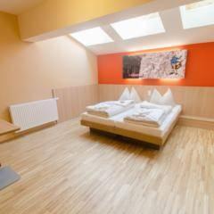Doppelbett im Doppelzimmerl mit Dachfenster im JUFA Hotel Altenmarkt. Der Ort für erholsamen Familienurlaub und einen unvergesslichen Winterurlaub.