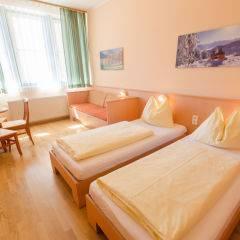 Doppelbett in einem Doppelzimmer mit TV im JUFA Hotel Kaprun. Der Ort für erholsamen Familienurlaub und einen unvergesslichen Winter- und Wanderurlaub.