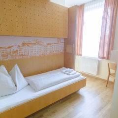Bett im Einzellzimmer im JUFA Hotel Salzburg City mit Fenster. Der Ort für erlebnisreichen Städtetrip für die ganze Familie und der ideale Platz für Ihr Seminar.