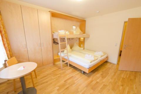 Betten im Appartement im JUFA Hotel Montafon mit Tisch. Der Ort für erholsamen Familienurlaub und einen unvergesslichen Winter- und Wanderurlaub.