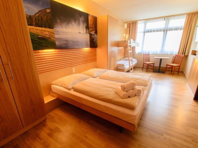 Betten im Familienzimmer large im JUFA Hotel Almtal mit TV. Der Ort für erholsamen Familienurlaub und einen unvergesslichen Winter- und Wanderurlaub.