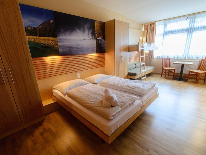 Doppelbett im Familienzimmer medium im JUFA Hotel Almtal mit Fenster. Der Ort für erholsamen Familienurlaub und einen unvergesslichen Winter- und Wanderurlaub.