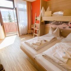 Betten im Familienzimmer medium im JUFA Hotel Altenmarkt mit Balkon. Der Ort für erholsamen Familienurlaub und einen unvergesslichen Winterurlaub.