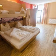 Betten im Familienzimmer xlarge im JUFA Hotel Altenmarkt mit Balkontür. Der Ort für erholsamen Familienurlaub und einen unvergesslichen Winterurlaub.