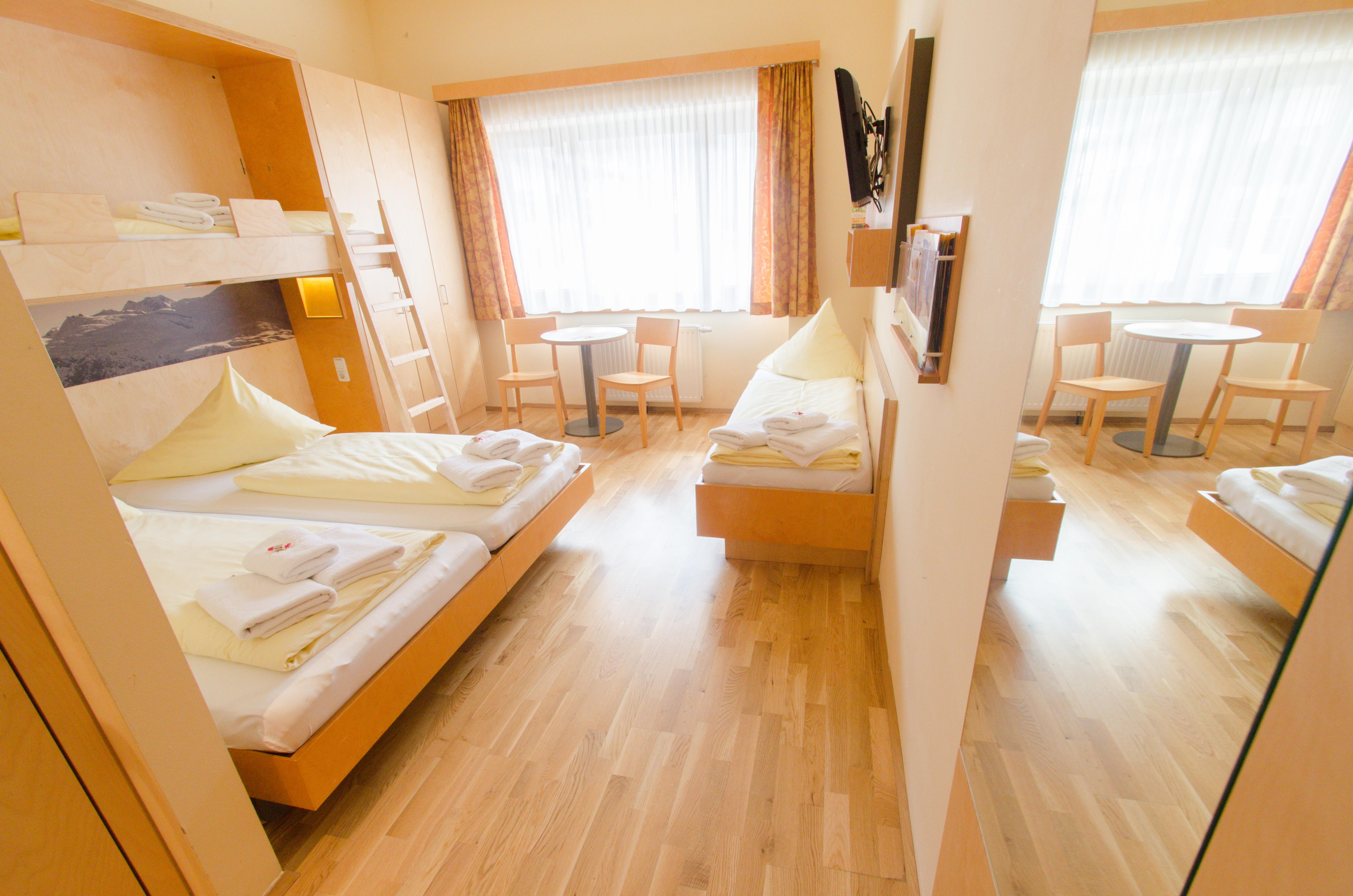 Betten im Familienzimmer large im JUFA Hotel Montafon mit Spiegel. Der Ort für erholsamen Familienurlaub und einen unvergesslichen Winter- und Wanderurlaub.
