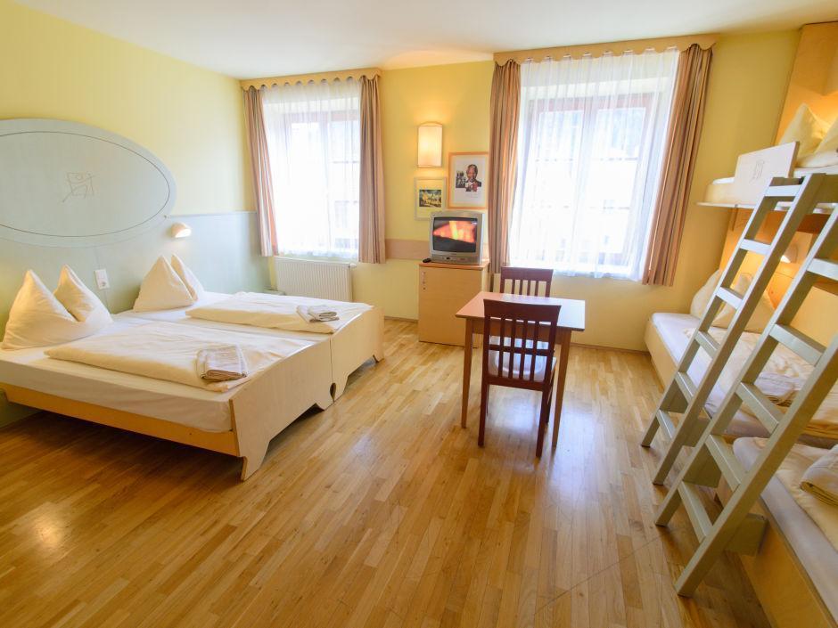 Betten im Familienzimmer xxlarge im JUFA Hotel Oberwölz mit Tisch. Der Ort für erholsamen Familienurlaub und einen unvergesslichen Winter- und Wanderurlaub.