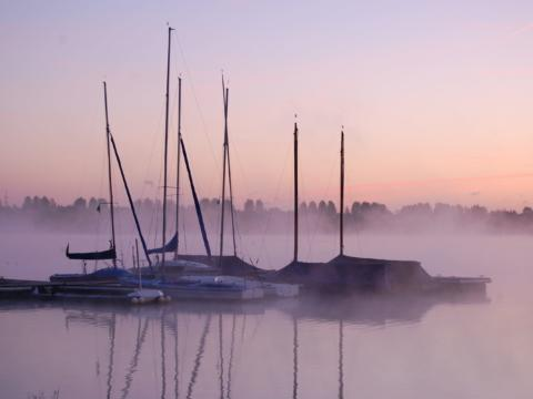Sie sehen Segelboote im Nebel am Blausteinsee in Nordreihn-Westfalen. JUFA Hotels bietet Ihnen den Ort für erlebnisreichen Natururlaub für die ganze Familie.
