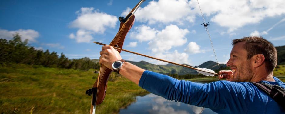 Mann beim Bogenschiessen im Robin Hood Land in Schladming-Dachstein in der Nähe von JUFA Hotels. JUFA Hotels bietet erholsamen Familienurlaub und einen unvergesslichen Winter- und Wanderurlaub.