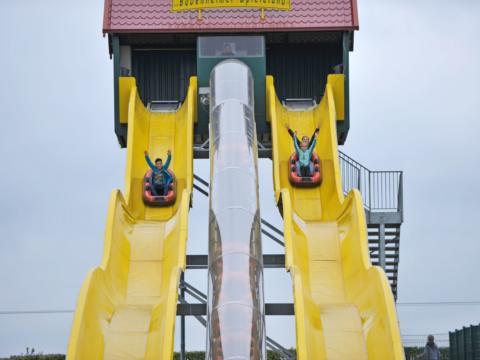 Kinder rutschen mit Rutschbooten auf zwei parallell stehenden gelben Wasserrutschen im Bubenheimer Spieleland. JUFA Hotels bietet kinderfreundlichen und erlebnisreichen Urlaub für die ganze Familie.