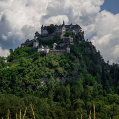 Burg Hochosterwitz in Kärnten von der Ferne mit Feld und Wolken in der Nähe von JUFA Hotels. Der Ort für erholsamen Familienurlaub und einen unvergesslichen Winter- und Wanderurlaub.